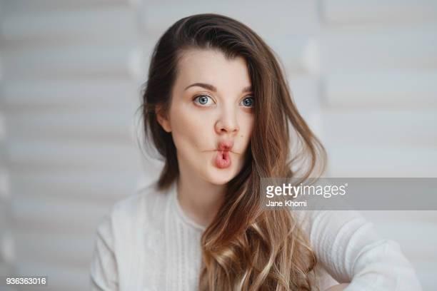beautiful caucasian ethnicity woman makes funny face - caras raras fotografías e imágenes de stock