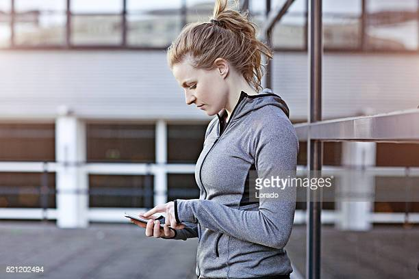 Beautiful caucasian sporty athletic woman checking smartphone in urban setting