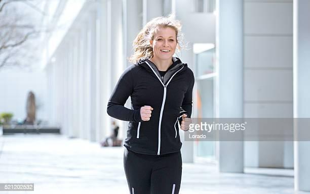 Beautiful caucasian sporty athletic woman jogging in urban setting