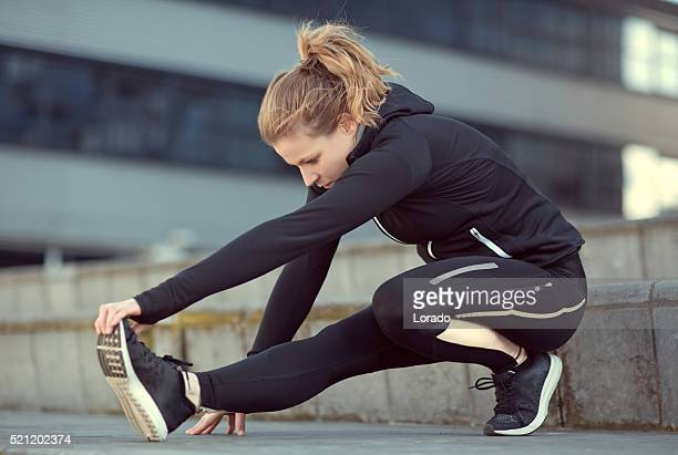 beautiful caucasian sporty athletic woman stretching in urban setting - warming up stock pictures, royalty-free photos & images