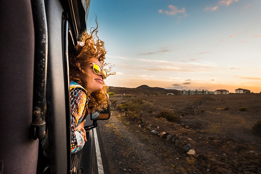 beautiful caucasian young woman travel outside the car with wind in the curly hair, motion and movement on the road discovering new places during a nice sunset, enjoy and joyful freedom concept 972155284