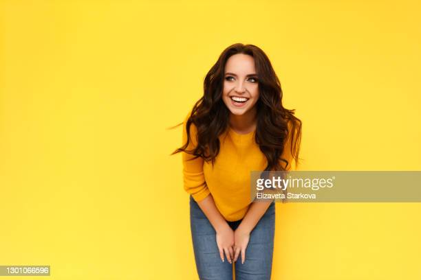 beautiful cheerful emotional laughing smiling curly-haired brunette woman in orange sweater having fun and looking away on bright yellow isolated background - オレンジ色のシャツ ストックフォトと画像