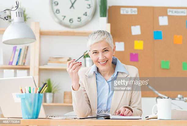 Beautiful cheerful mature woman at office working