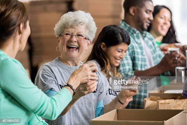Beautiful cheerful senior woman volunteers at food bank