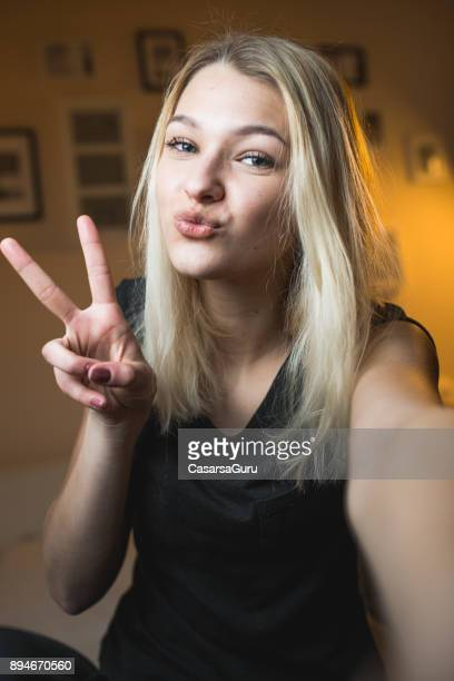 Beautiful Cheerful Teenage Girl Taking a Selfie in Bedroom