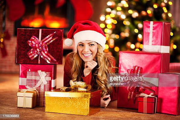 Beautiful cheerful woman surrounded by Christmas presents.