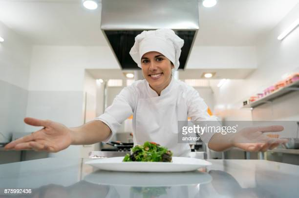 Beautiful chef showing off an appetizer she just made looking very proud