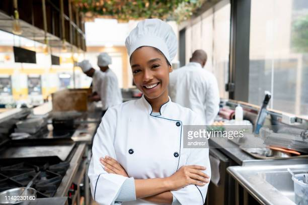 beautiful chef working in a kitchen at a restaurant - chef stock pictures, royalty-free photos & images
