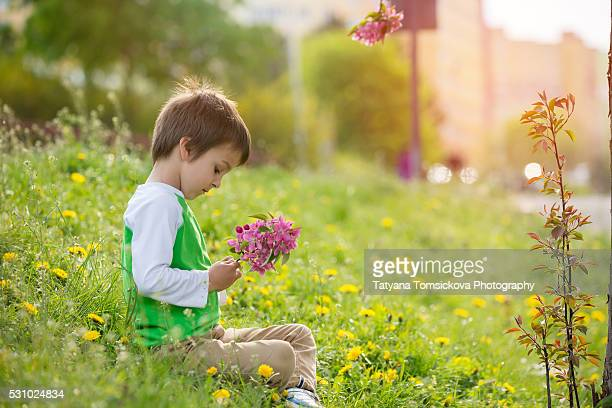 Beautiful child picks flowers and play with them on a spring green meadow