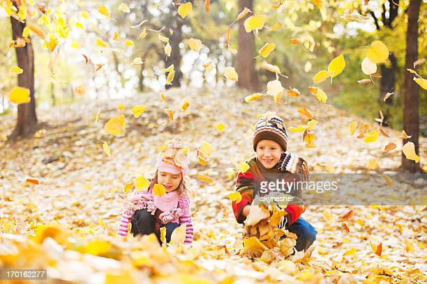 Beautiful children playing in the heap of leaves.