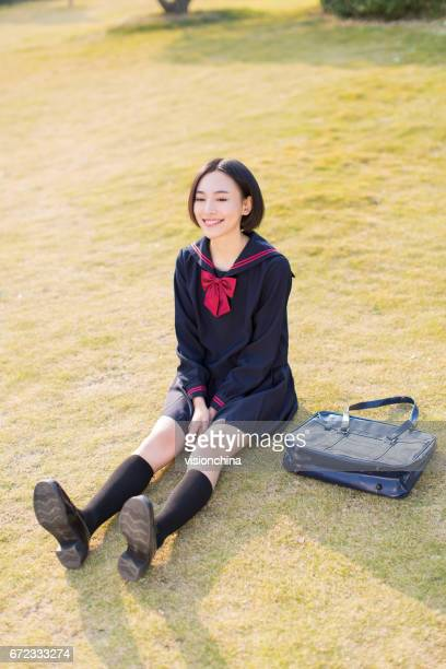 beautiful chinese female student, carrying a shoulder bag in the park