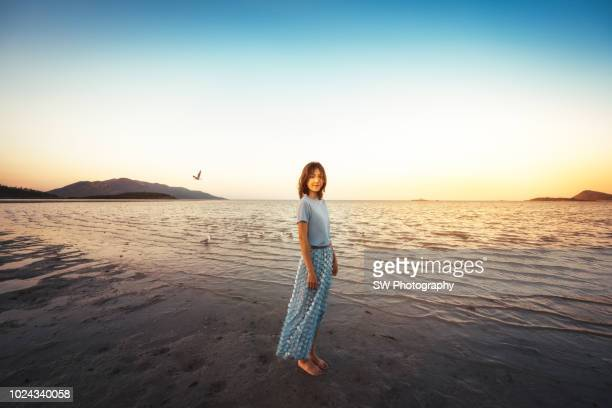 beautiful chinese woman standing on the beach - grande angular - fotografias e filmes do acervo