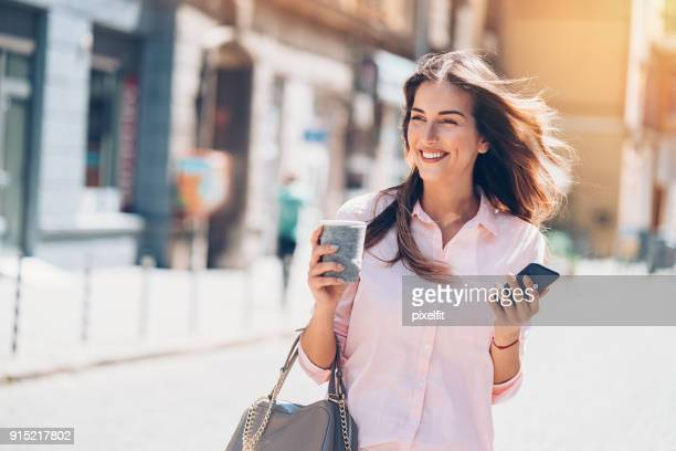 Beautiful city woman with phone and coffee
