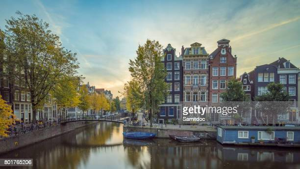 Beautiful cityscape in Amsterdam, Netherlands. Reflected city lights in water with blue sky.