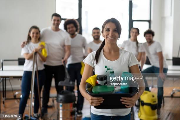 カメラに笑顔のクリーニング製品でバケツを持っているオフィスで彼女のチームと美しいクリーニングの女性 - 清掃用具 ストックフォトと画像