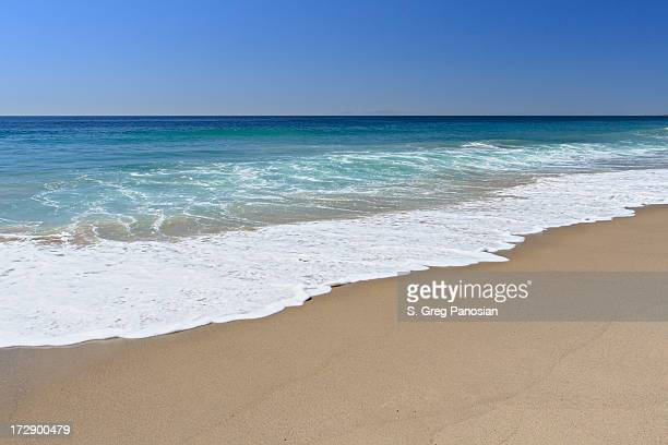 Beautiful clear beach with waves coming to the shoreline