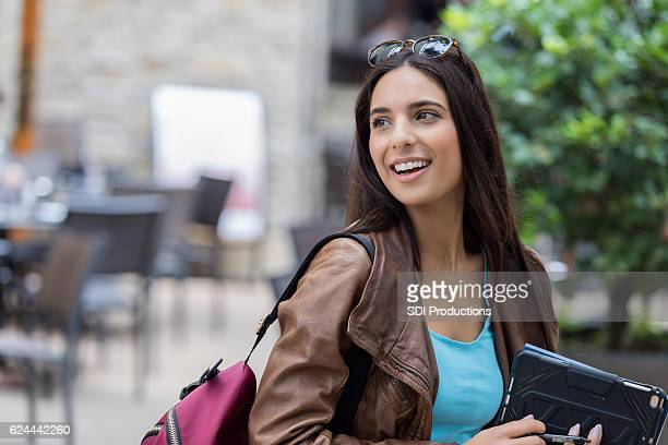Beautiful college coed smiles while leaving coffee shop