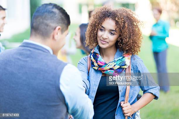 Beautiful college student shaking hands with professor on campus