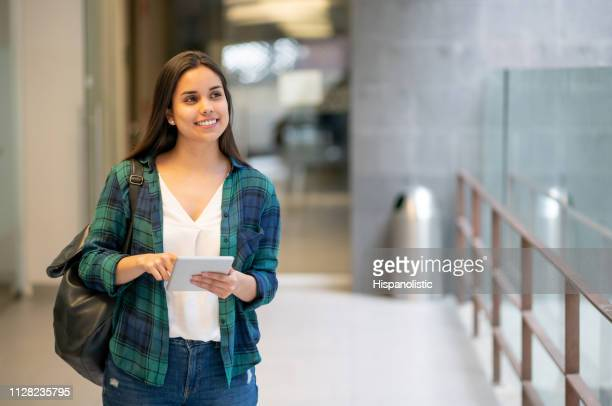 beautiful college student walkign towards class holding her tablet looking away daydreaming - academy stock pictures, royalty-free photos & images