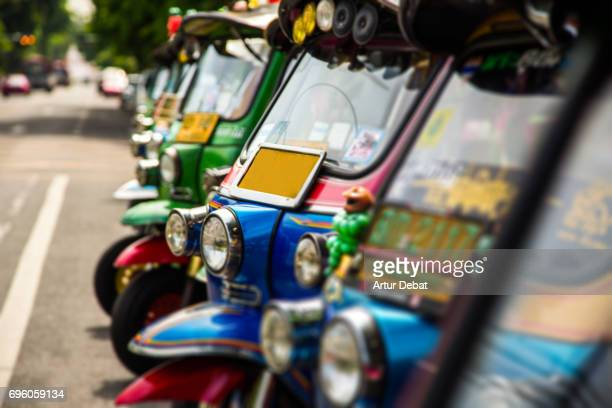 beautiful colorful tuk tuk rickshaw in the streets on bangkok during day. - rickshaw stock photos and pictures
