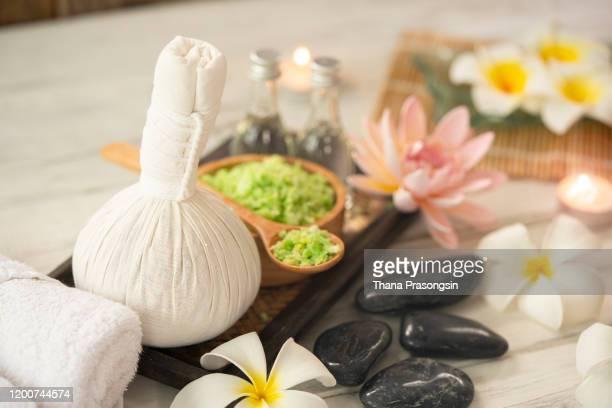 beautiful composition of spa treatment on wooden table - thai massage stockfoto's en -beelden
