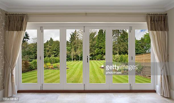 beautiful concertina doors with garden view - english culture stock pictures, royalty-free photos & images