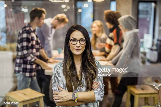Beautiful confident business leader with crossed arms looking at camera.