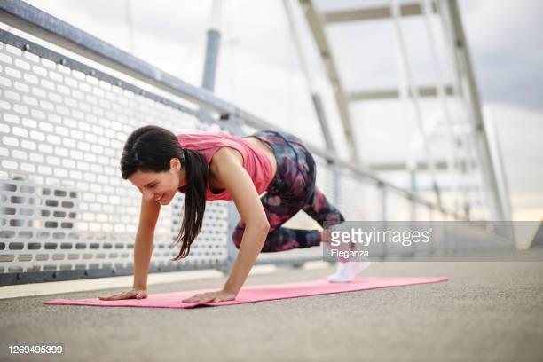 belle femme confiante forte forme physique dans une tenue athlétique fait des exercices d'escalade à l'extérieur - fessier femme photos et images de collection