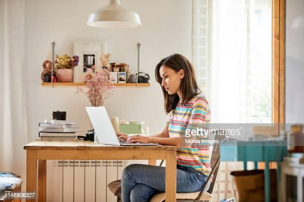 テーブルでノートパソコンを使用して、美しい自信を持って女性 - 足を組む ストックフォトと画像