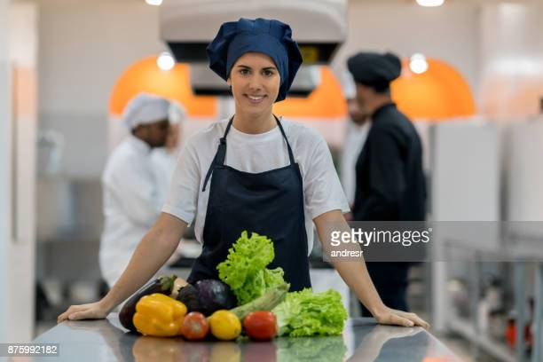 Beautiful cooking assistant at an industrial kitchen looking at camera smiling