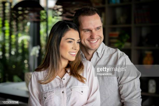 Beautiful couple at home ebracing each other and looking away daydreaming