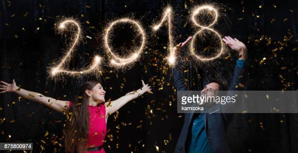 Beautiful couple celebrating New Year's Eve with sparkler 2018
