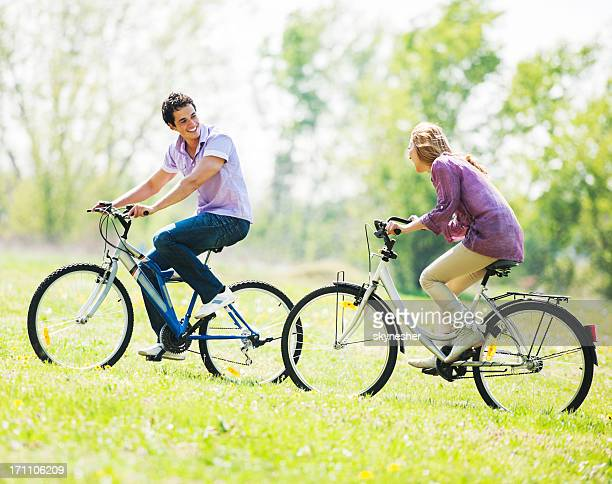 Beautiful couple cycling in the field.