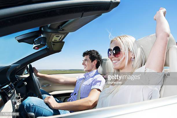 Beautiful couple driving in their Convertible car.