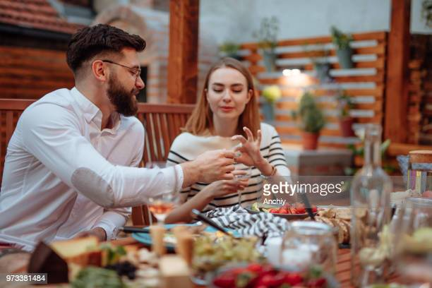 Beautiful couple eating cheese in a summer garden