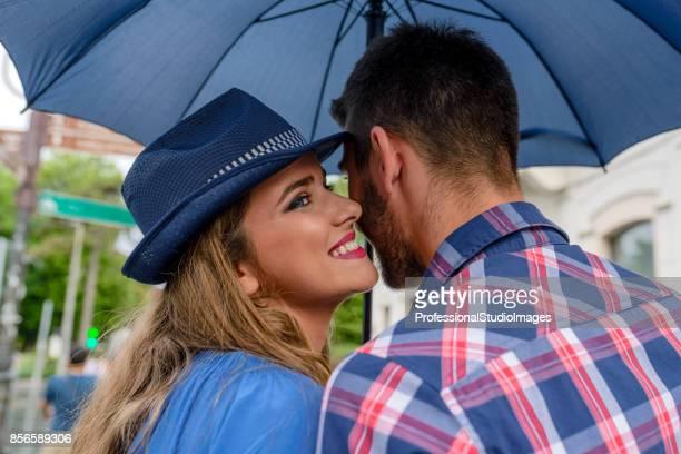 Beau couple bénéficiant en jour de pluie dans le parc public.