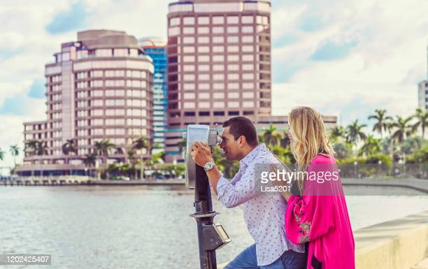 beautiful couple explore new city and look through tower viewer - west palm beach stock pictures, royalty-free photos & images