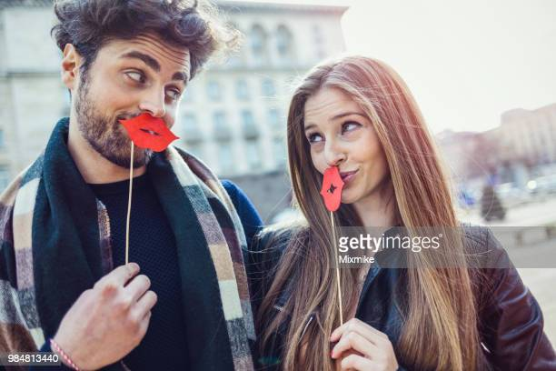 beautiful couple grimacing with enormous red lips - big lips stock photos and pictures