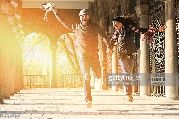 Beautiful couple holding hands and jumping under ancient columns