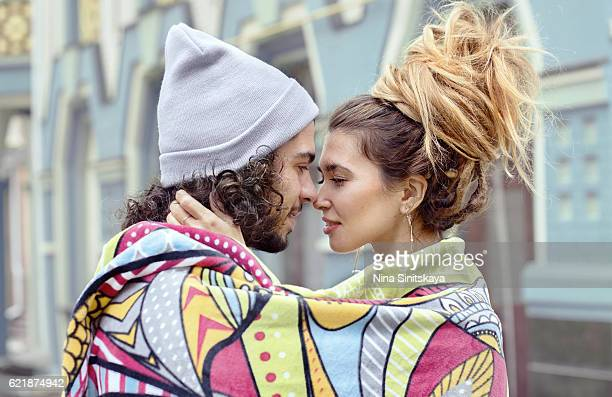 beautiful couple hugging wrapped up in the rug outdoors - love at first sight stock pictures, royalty-free photos & images