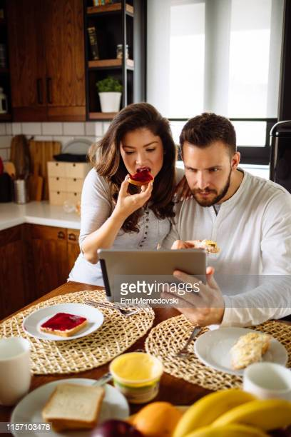 Beautiful couple in kitchen using digital tablet