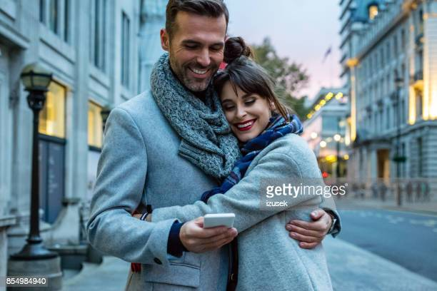 Beautiful couple in London street in the evening, man using smart phone