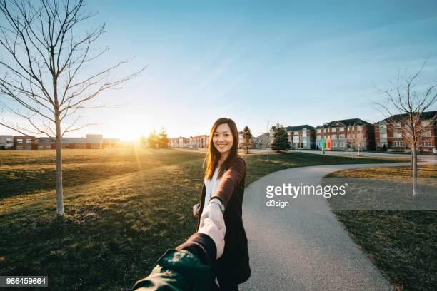 beautiful couple in love holding hands and relaxing in park at sunset - following stock pictures, royalty-free photos & images