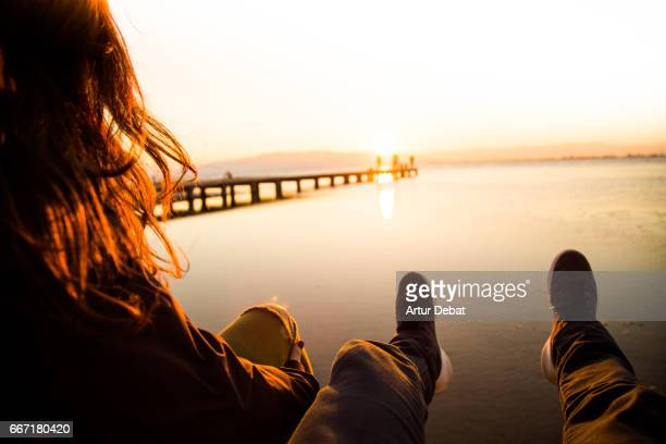 Beautiful couple in love sitting and contemplating the sunset over the Ebro Delta in the Mediterranean sea from wood pier and stunning sunlight during a weekend travel in the region.