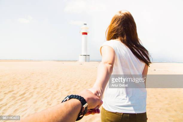 Beautiful couple in love traveling in the Ebro Delta region. Girl is leading the way to the beautiful white lighthouse in the middle of the beach in a warm and sunny day and boyfriend is holding hands and following her. Follow me serie.