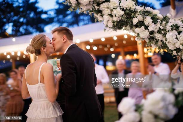 beautiful couple is kissing at the celebration - ceremony stock pictures, royalty-free photos & images