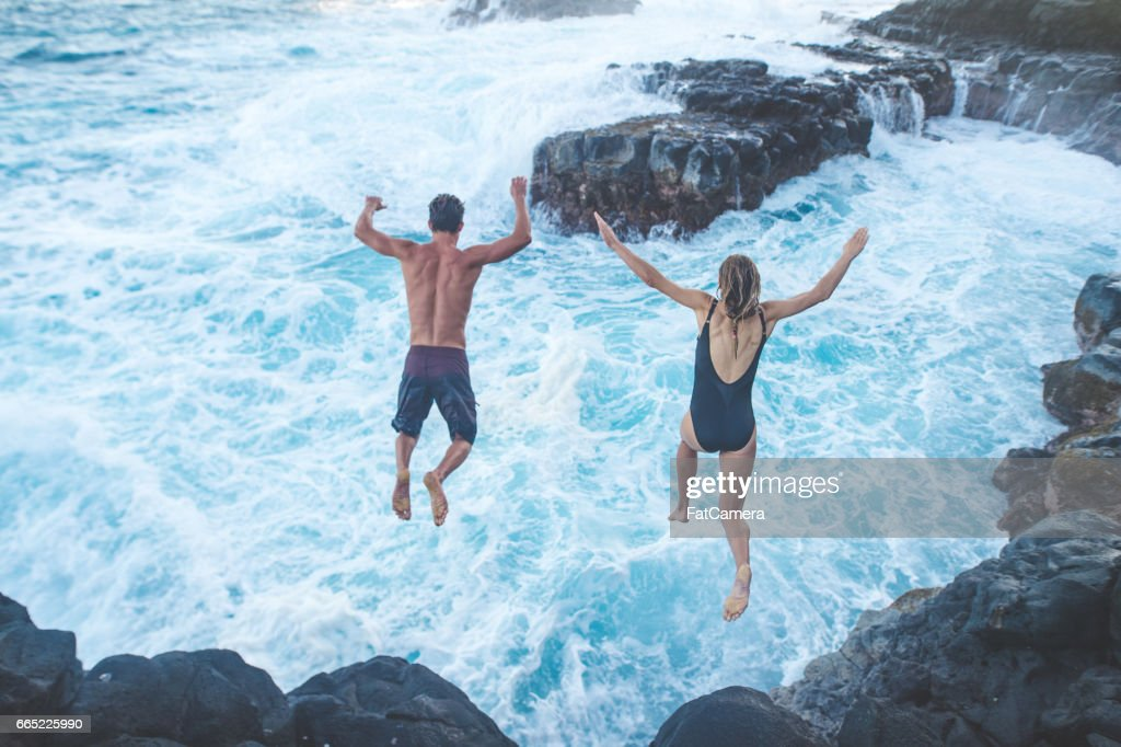 Beautiful couple jumping off cliff into ocean : Stock Photo