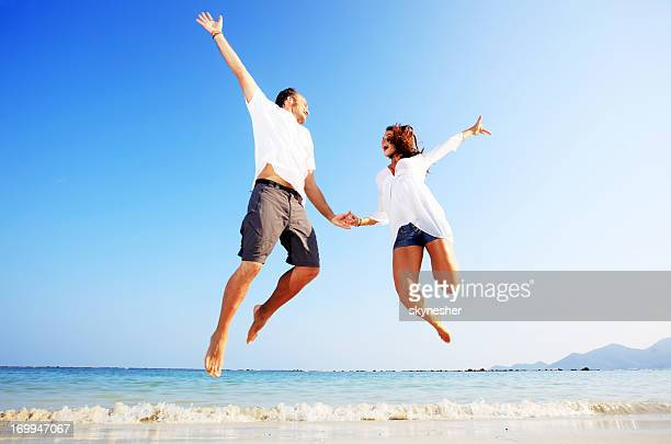 Beautiful couple jumping on the beach.