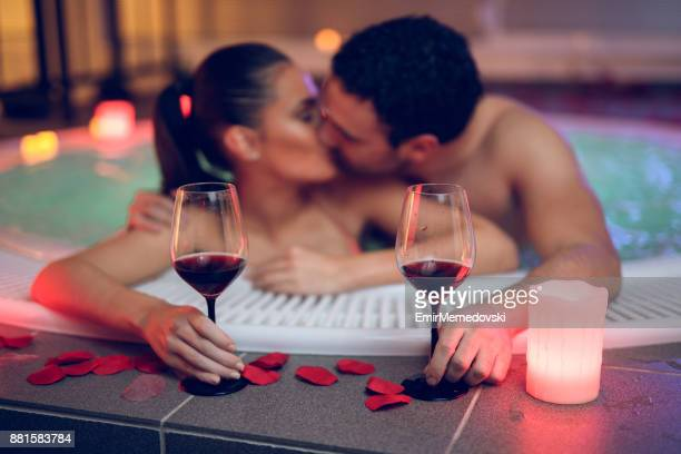 beautiful couple kissing in hot tub at health spa - bacio sulla bocca foto e immagini stock
