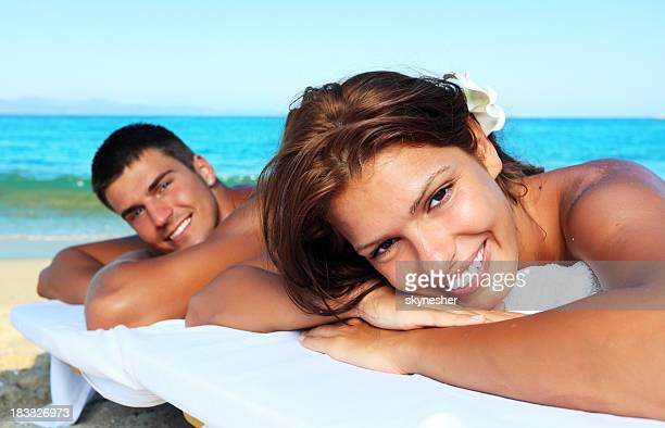 Beautiful couple lying after a massage at the beach.